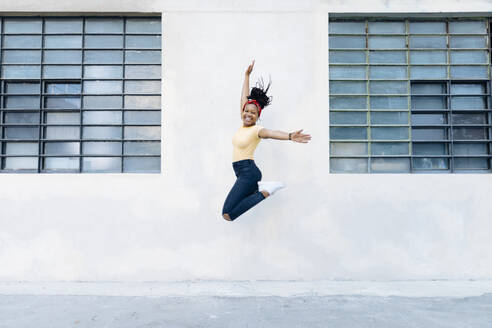 Happy young woman jumping in the air in front of white wall - SODF00004