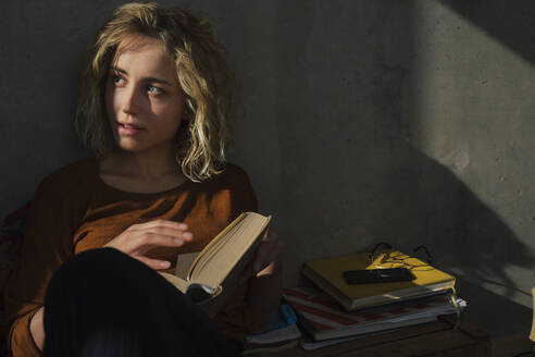 Blond student sitting on bed with a book looking at distance - GCF00268