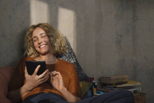 Portrait of happy young woman lying on bed with E-book reader - GCF00274