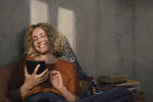 Stundentin liest E-Book-Reader auf dem Bett, Wohnung, Deutschland, Berlin, Studentin im WG-Zimmer - GCF00274
