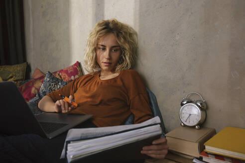 Stundentin arbeitet auf dem Bett, Wohnung, Deutschland, Berlin, Studentin im WG-Zimmer - GCF00289