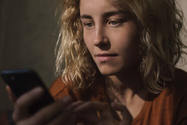 Portrait of blond young woman using cell phone - GCF00298