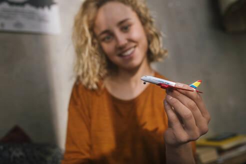 junge Frau mit Spielzeug-Flugzeug, Wohnung, Deutschland, Berlin, Studentin im WG-Zimmer - GCF00304