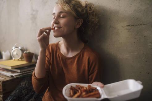 junge Frau isst Pommers, Wohnung, Deutschland, Berlin, Studentin im WG-Zimmer - GCF00310