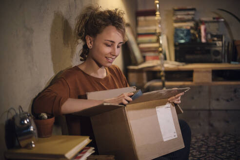 Smiling young woman unpacking parcel at home - GCF00313