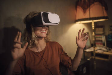 Young woman using Virtual Reality Glasses at home - GCF00319