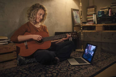 Smiling young woman sitting on the floor with guitar looking at laptop - GCF00331