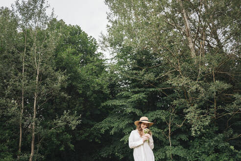 Lithuania, Vilnius, Woman with a hat in front of the forest with a bouquet of flowers - AHSF00584