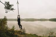 Man hanging on rope swing at remote lake - BLEF10285