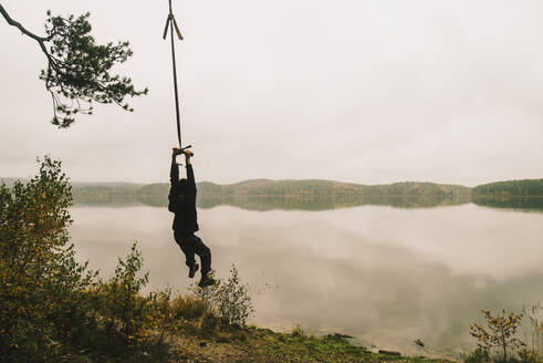 Man hanging on rope swing at remote lake - BLEF10285