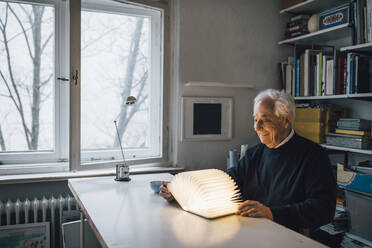 Senior man with glowing book on table at home - GUSF02035