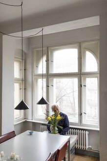Senior man with bunch of flowers sitting at table at home - GUSF02038