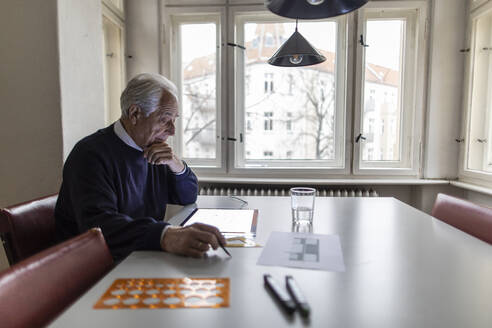 Senior man using tablet with architectural plan - GUSF02062