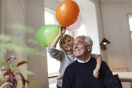 Happy grandfather and grandson playing with balloons at home - GUSF02086