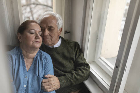 Portrait of affectionate senior couple at the window - GUSF02122