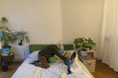 Happy grandfather playing with grandson on bed at home - GUSF02128