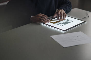 Close-up of senior man using tablet with architectural plan - GUSF02140
