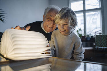 Happy grandfather and grandson looking at glowing book at home - GUSF02152