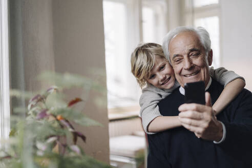 Happy grandfather and grandson using cell phone at home - GUSF02164