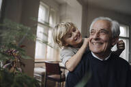Happy grandson pulling grandfather's ears at home - GUSF02170