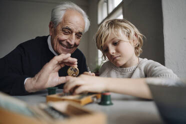 Watchmaker and his grandson examining watch together - GUSF02179