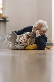 Happy grandfather and grandson lying on the floor at home using a tablet - GUSF02185