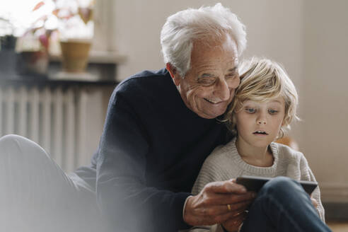 Grandfather and grandson using a tablet at home - GUSF02188