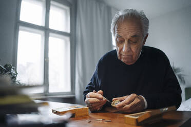 Senior man repairing a watch at home - GUSF02194