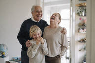 Laughing grandparents with grandson at home - GUSF02200