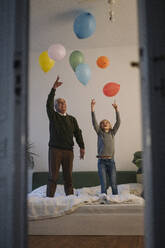 Happy grandfather and grandson playing with balloons on bed at home - GUSF02209