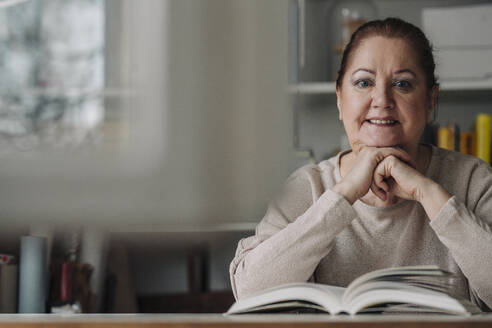 Portrait of smiling senior woman with book at home - GUSF02230