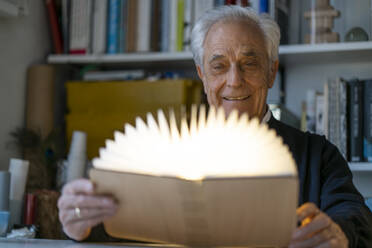 Senior man with glowing book at home - GUSF02239