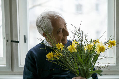 Senior man with bunch of flowers at home - GUSF02242