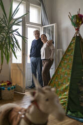 Senior couple standing at the window in children's room - GUSF02257