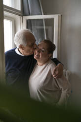 Happy senior couple kissing at the window at home - GUSF02260