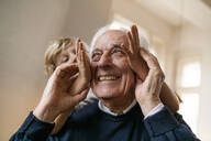 Playful grandson with grandfather at home - GUSF02269