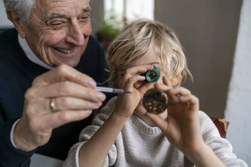 Watchmaker and his grandson examining watch together - GUSF02275