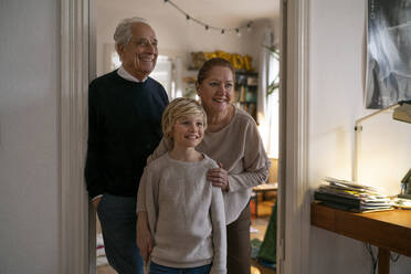 Portrait of happy grandparents with grandson at home - GUSF02278