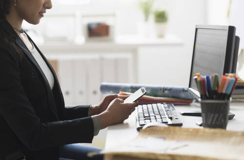 Mixed race businesswoman using cell phone at desk - BLEF10410