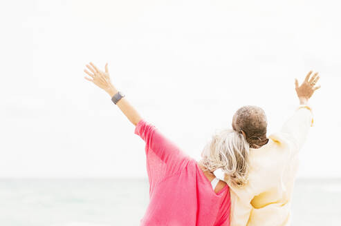Older couple cheering and hugging on beach - BLEF10425