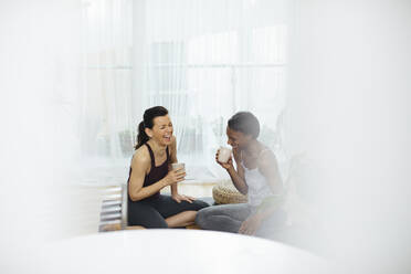 Two happy women sitting on gym mat and drinking tea at home - SODF00015