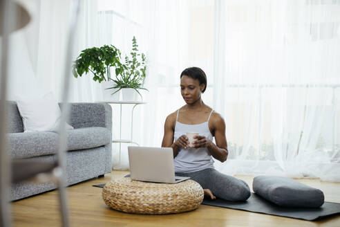 Woman sitting on gym mat at home using laptop - SODF00018