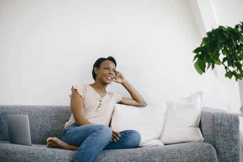 Smiling woman sitting on couch at home with laptop - SODF00030