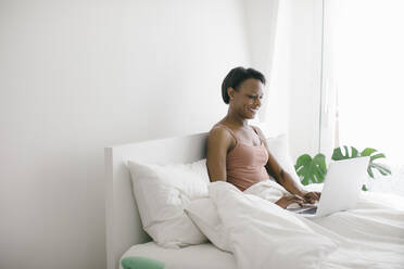 Smiling woman lying in bed at home using laptop - SODF00033