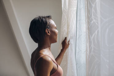 Woman at home looking out of window - SODF00048