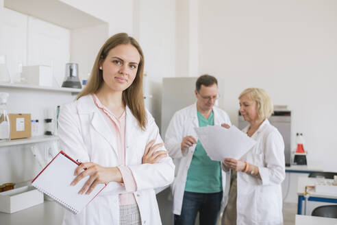 Lithuania, Vilnius, Portrait of young researcher in white coat in a lab - AHSF00616