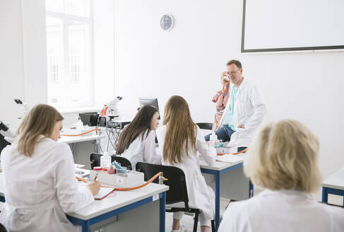 Lithuania, Vilnius, Students having lecture with professor in science lab classroom - AHSF00637