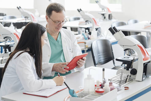 Lithuania, Vilnius, Scientists in white coats using tablet in lab - AHSF00682