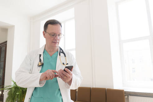 Lithuania, Vilnius, Doctor using smartphone in a corridor of hospital - AHSF00688