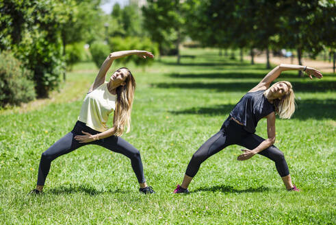 Mature woman doing yoga with her daughter in a park - JSMF01144
